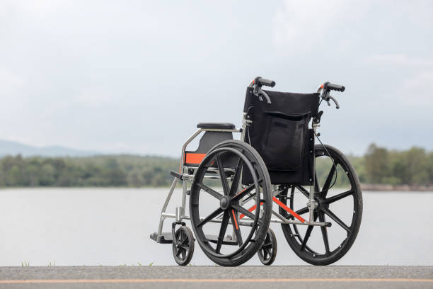 Empty wheelchair on lake stock photo