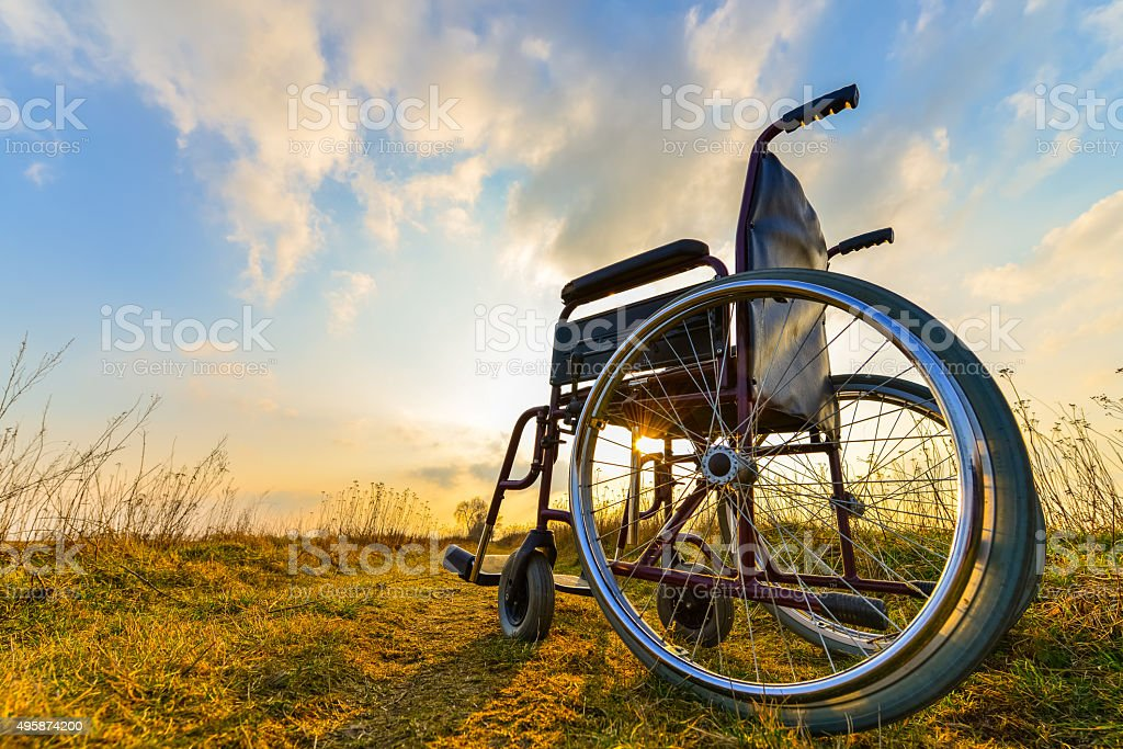 Empty wheelchair on the meadow at sunset royalty free stockfoto