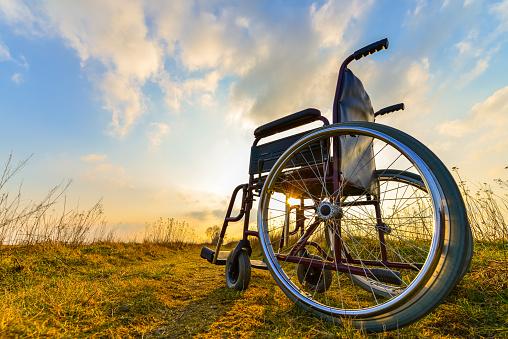 Empty Wheelchair On The Meadow At Sunset Stockfoto en meer beelden van 2015