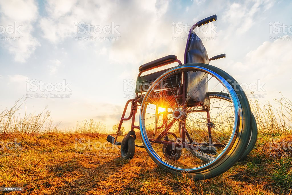 Empty wheelchair on the meadow at sunset stock photo