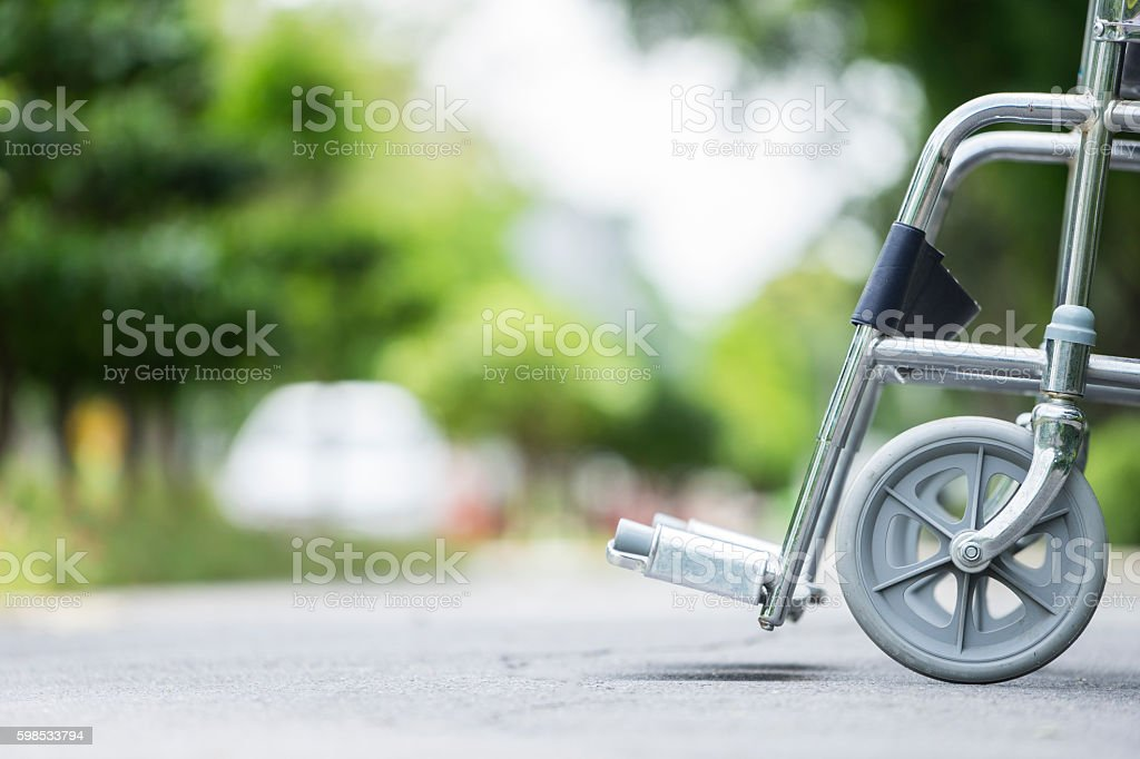 Empty wheelchair parked in park stock photo