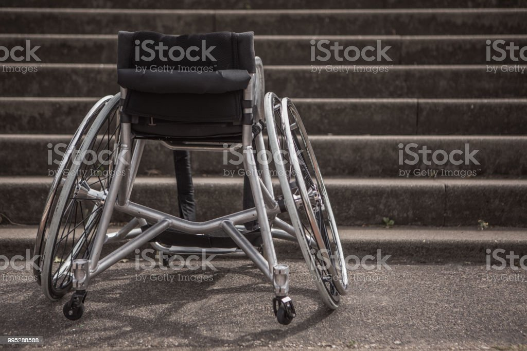 Empty wheelchair stuck before stairs stock photo