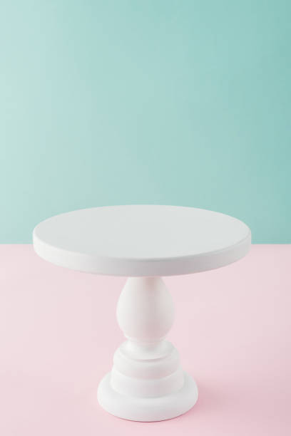 empty white cake stand on pink and turquoise background with copy space empty white cake stand on pink and turquoise background with copy space cakestand stock pictures, royalty-free photos & images