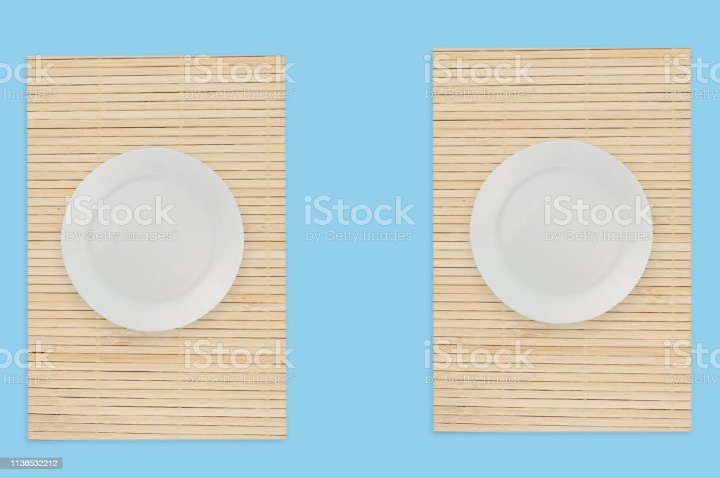 Empty white circle plate on bamboo mat on blue table. Top view....
