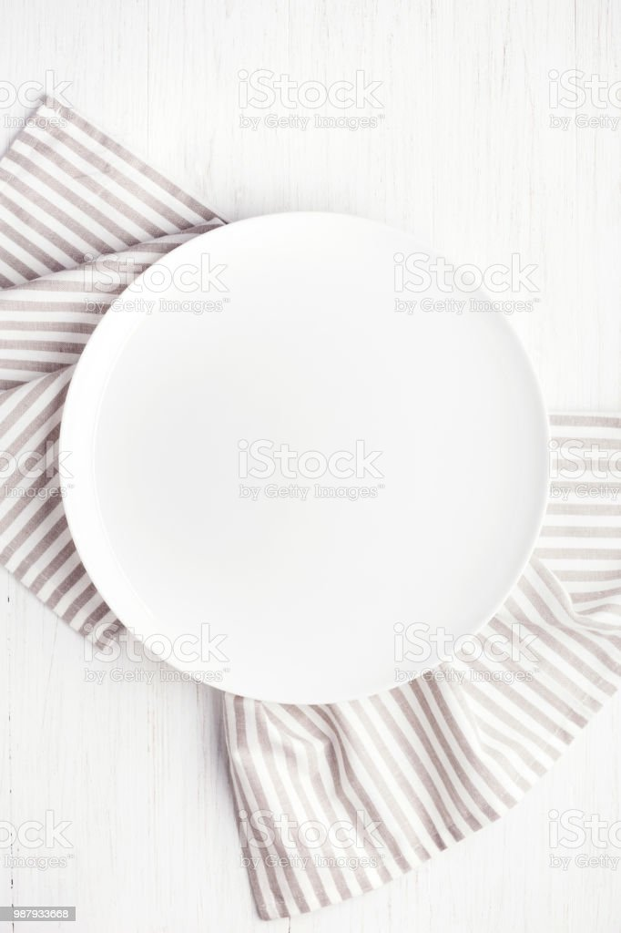 Empty white circle plate on wooden table with linen napkin. Overhead...