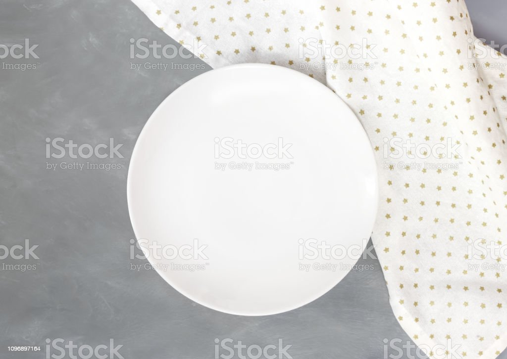Empty white circle plate on dark gray cement table with linen napkin....