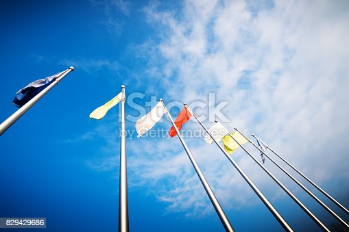 istock Empty white clear flag waving against clean blue sky, close up, isolated with clipping path mask alpha channel transparency 829429686