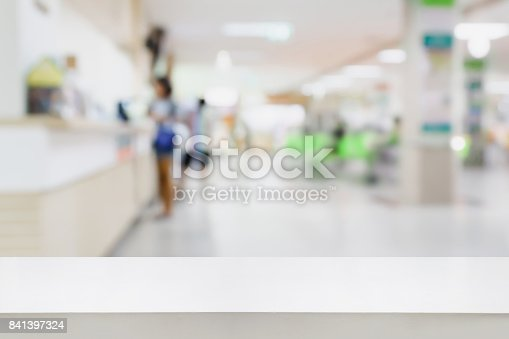 istock Empty white desk with blur hospital background 841397324