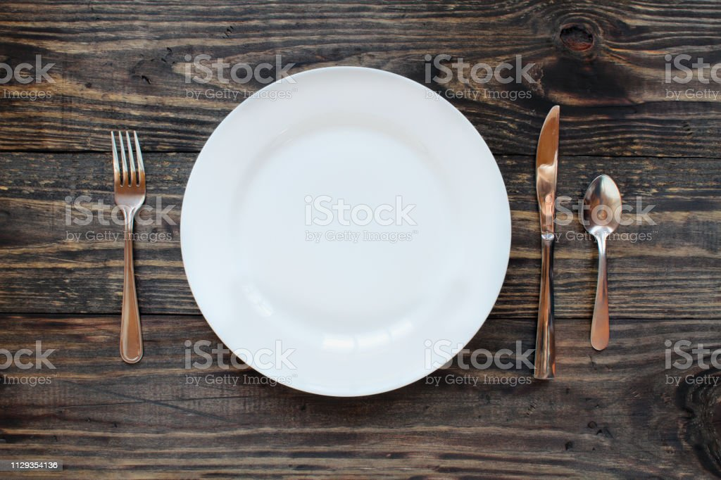 Empty white dinner plate over a rustic wooden table stock photo