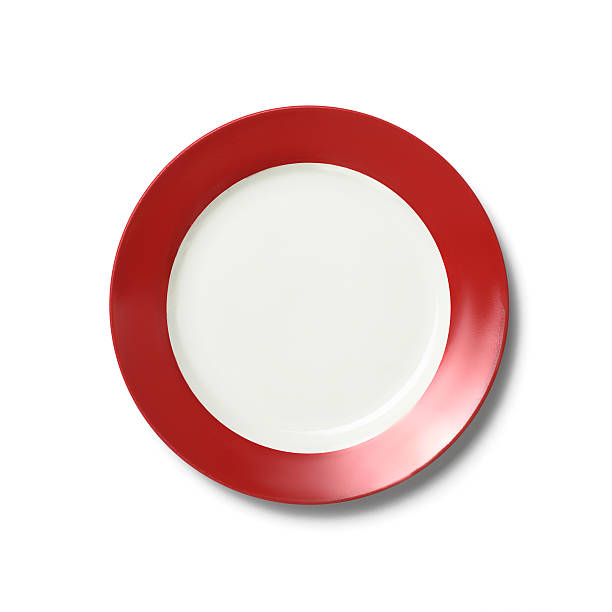 Empty white dinner plate with red rim on white background stock photo