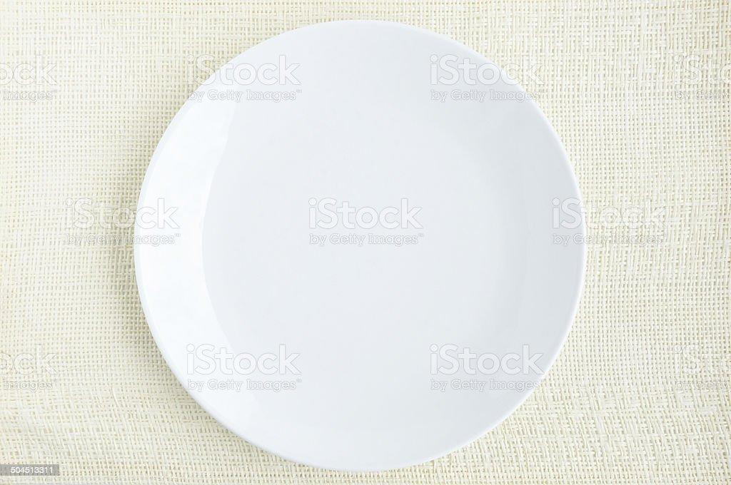Empty white dish on cream fabric table mat stock photo