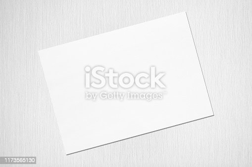 1173565159 istock photo Empty white horizontal rectangle poster mockup with soft shadow lying diagonally on neutral light grey textured background 1173565130