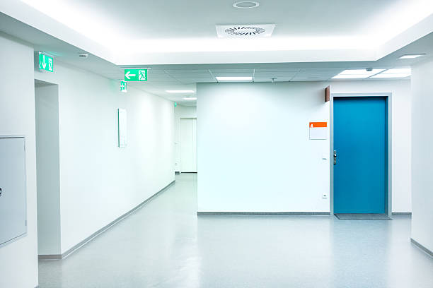 Empty white Hospital corridor with a blue door stock photo