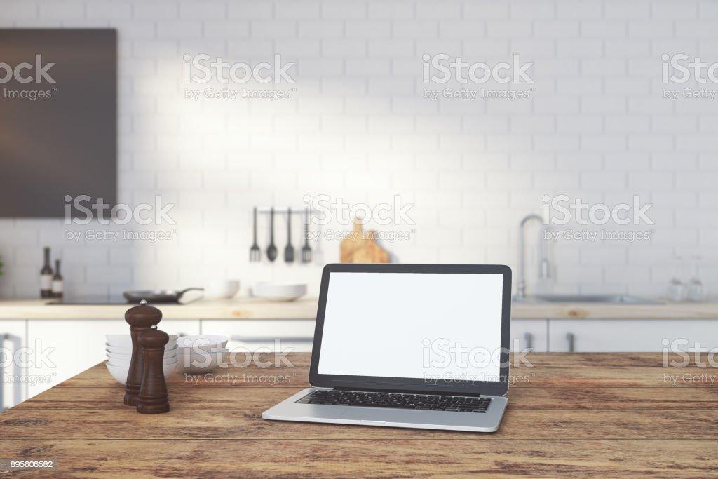 Empty white laptop on kitchen counter stock photo