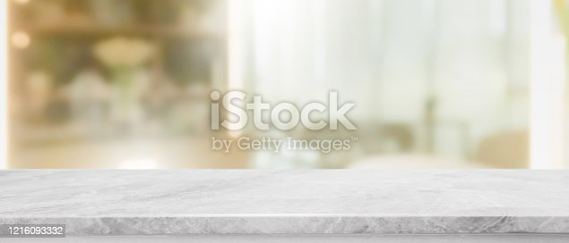 662984994 istock photo Empty white marble stone table top and blur glass window interior restaurant banner mock up abstract background - can used for display or montage your products. 1216093332
