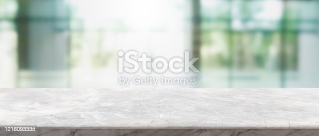 662984994 istock photo Empty white marble stone table top and blur glass window interior lobby and hall way banner mock up abstract background - can used for display or montage your products. 1216093335