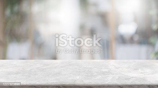 662984994 istock photo Empty white marble stone table top and blur glass window interior lobby and hall way banner mock up abstract background - can used for display or montage your products. 1227323895