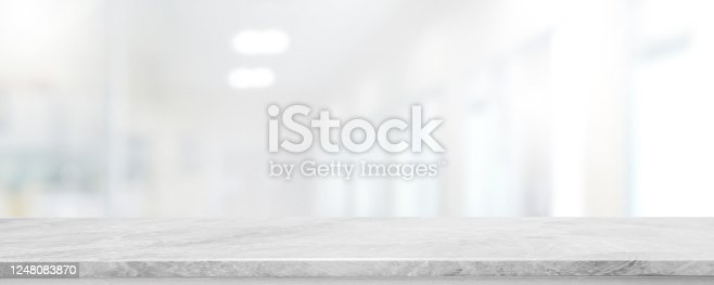 662984994 istock photo Empty white marble stone table top and blur glass window interior lobby and hall way banner mock up abstract background - can used for display or montage your products. 1248083870