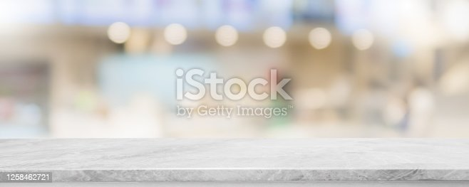 662984906 istock photo Empty white marble stone table top and blur glass window interior restaurant banner mock up abstract background - can used for display or montage your products. 1258462721