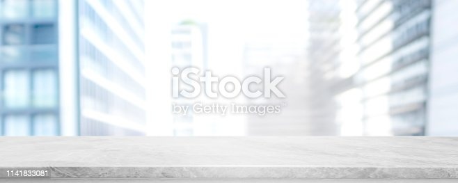 662984906istockphoto Empty white marble stone table top and blur glass window wall building banner mock up background - can used for display or montage your products. 1141833081