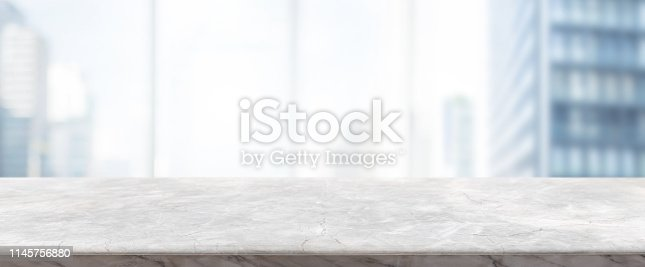 662984994 istock photo Empty white marble stone table top and blur glass window wall building banner mock up background - can used for display or montage your products. 1145756880