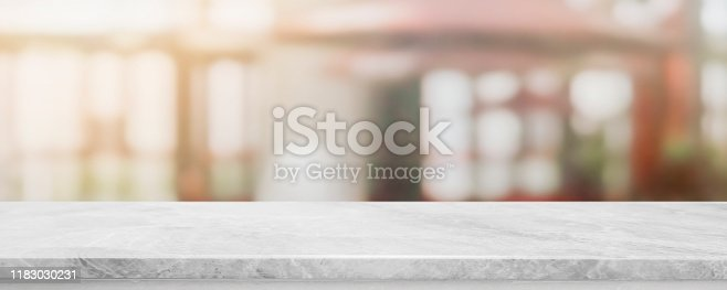 662984994 istock photo Empty white marble stone table top and blur glass window wall building banner mock up abstract background - can used for display or montage your products. 1183030231