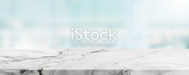 662984994 istock photo Empty white marble stone table top and blur glass window wall building banner mock up abstract background - can used for display or montage your products. 1183030237