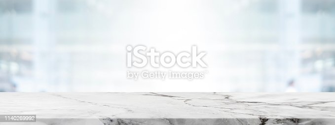 662984906istockphoto Empty white marble stone table top and blur glass window wall in office building background - can used for display or montage your products. 1140269992