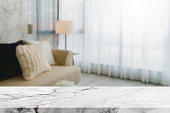 istock Empty white marble stone table top and blurred living room in home interior with curtain window background. - can used for display or montage your products. 1216093353