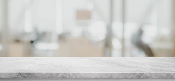 Empty white marble stone tabletop and blurred bokeh office interior space banner background - can used for display or montage your products. Empty white marble stone tabletop and blurred bokeh office interior space banner background - can used for display or montage your products. white marble stock pictures, royalty-free photos & images