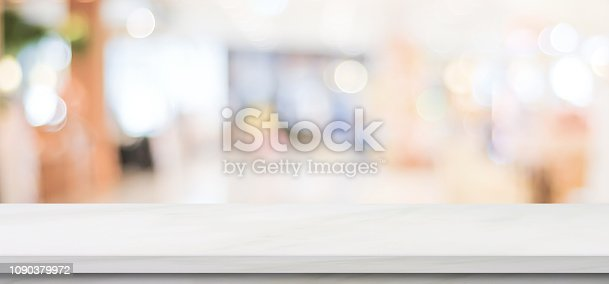 istock Empty white marble table over blur store background, banner, product display montage 1090379972