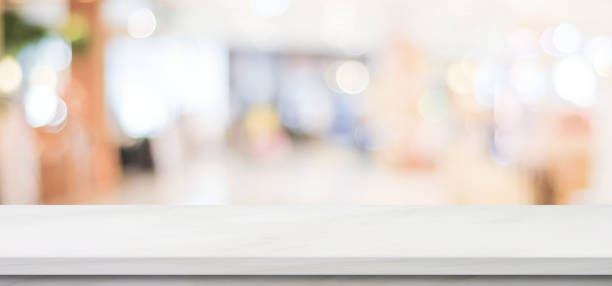Empty white marble table over blur store background, banner, product display montage stock photo