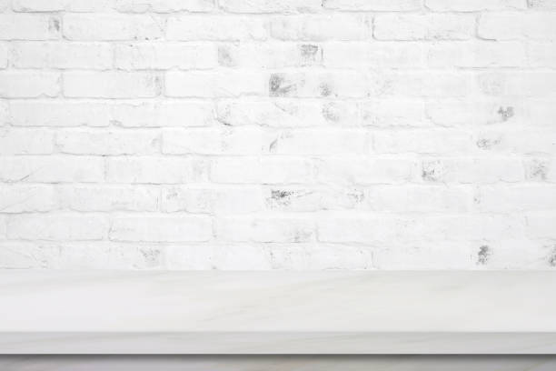Empty white marble table over brick wall background, product display montage stock photo