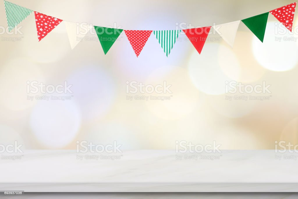 Empty white marble table over colorful party flags and blur bokeh background, new year, christmas, festival background, banner stock photo