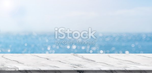 Empty white marble table top with blur blue sky and sea boekh background in sunny day,Mock up template for display or montage of product or content use as banner in social media ads.