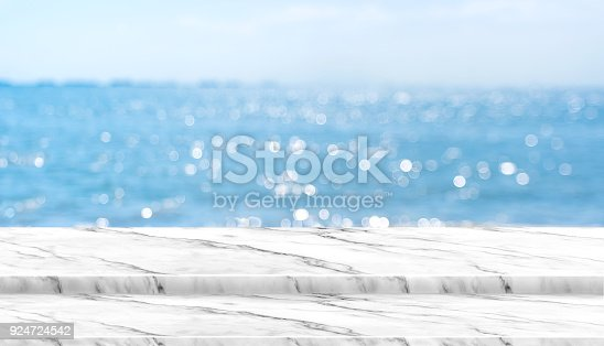 istock Empty white marble table top with blur blue sky and sea boekh background in sunny day,Mock up template for display or montage of product or content use as banner in social media ads 924724542