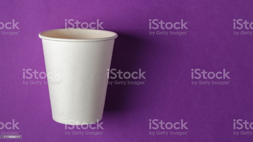 Disposable empty white paper cup on the vivid purple background