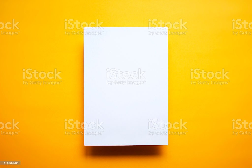Empty white paper sheet isolated yellow background - foto stock
