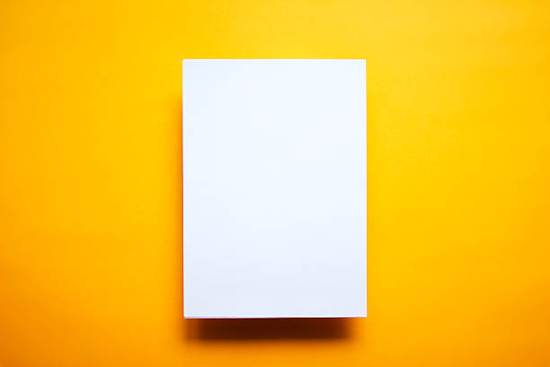 Empty white paper sheet isolated yellow background stock photo