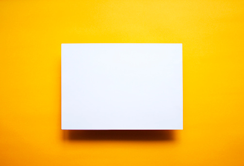 Empty White Paper Sheet Isolated Yellow Background Foto de stock y más banco de imágenes de Amarillo - Color