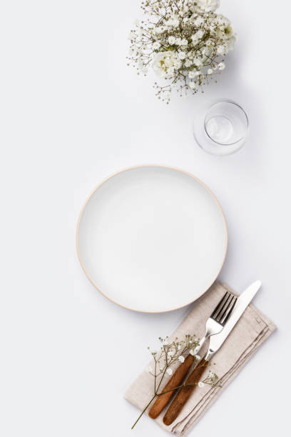 Empty white plate and cutlery on a napkin stock photo