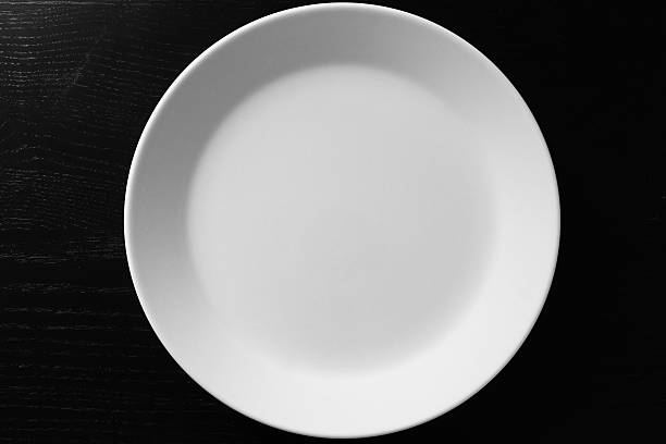 empty white plate on black wooden table - top view, wood table, empty imagens e fotografias de stock