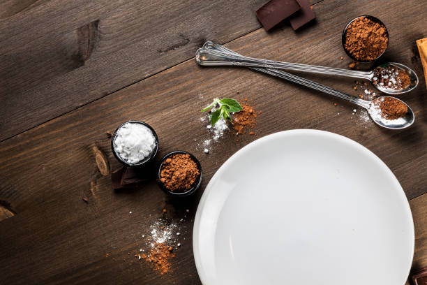 Empty white plate on dark wood, chocolate composition stock photo