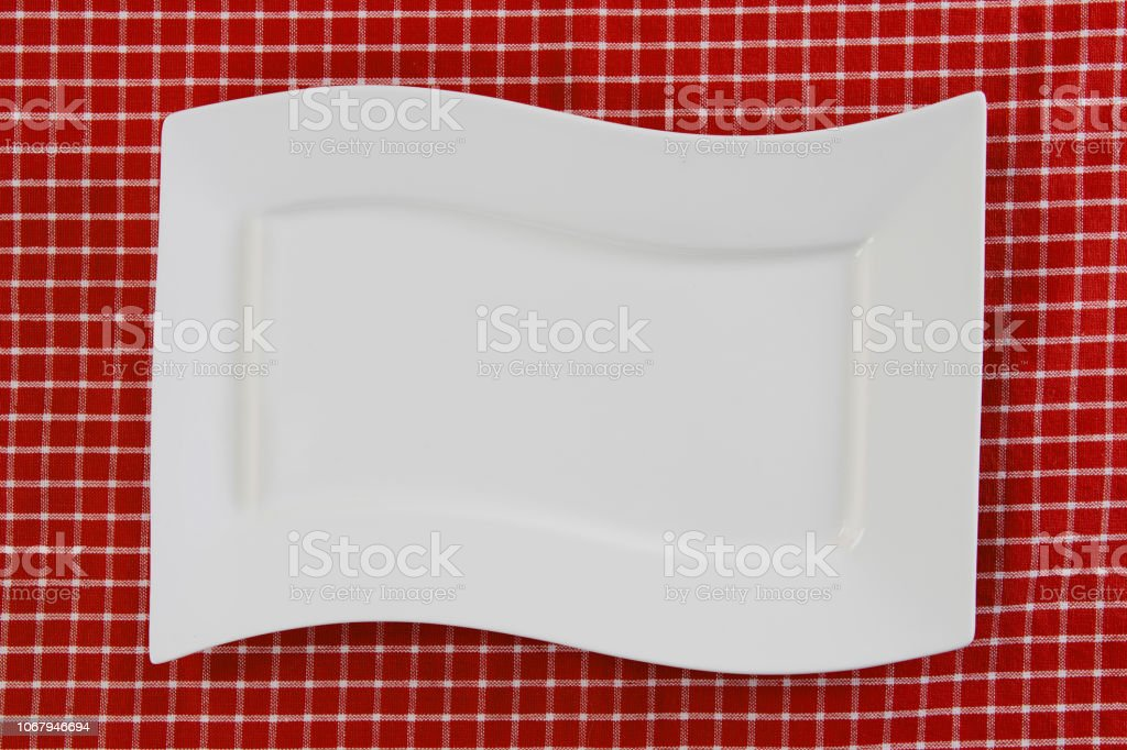 Empty white plate on red napkin or tablecloth. Top view. Template for...
