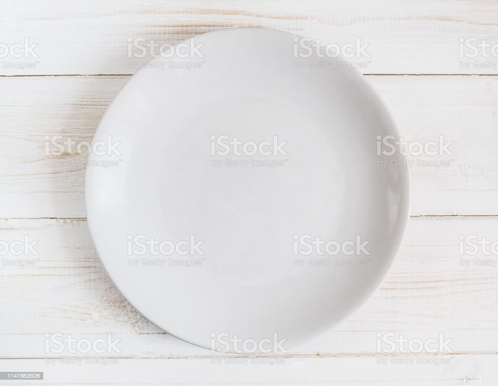 Empty white plate on white wooden background with shadow