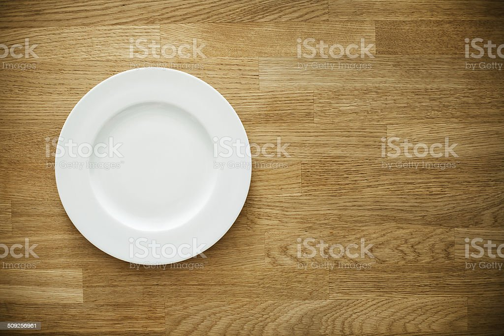 Empty white plate on wooden table stock photo