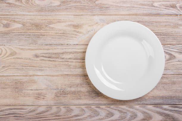 Empty white plate on wooden table. Template for your design. stock photo
