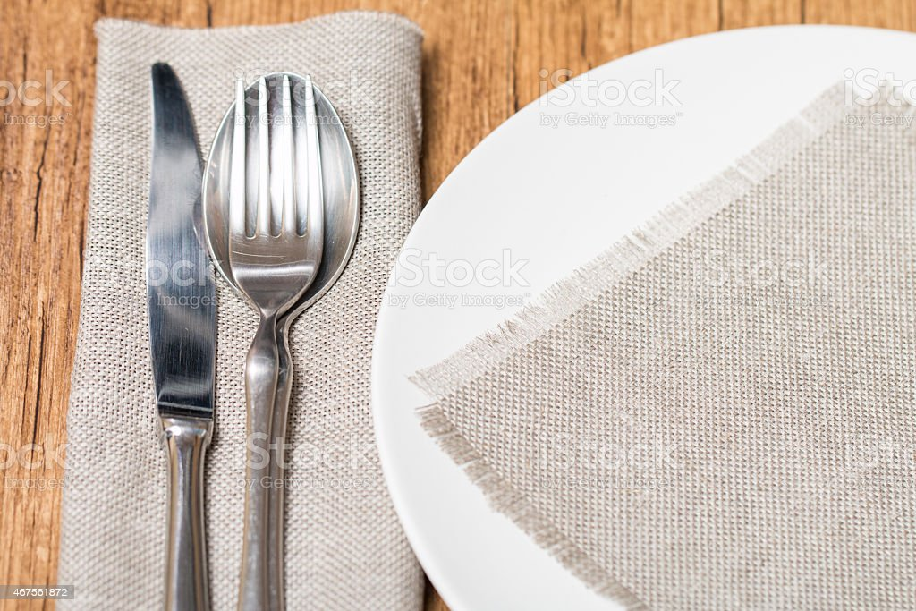 Empty white plate spoon, fork, knife stock photo