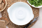 Empty white pot. On delicate beige tablecloth. Includes bread and green arugula. Concept to include your food and your text.