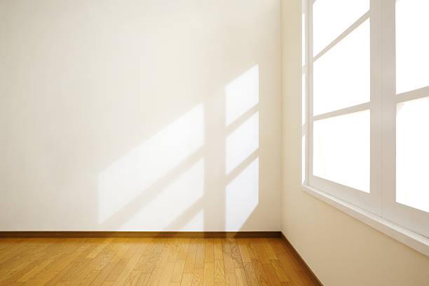 空のホワイトルームには、ウッドフロアーと自然光が差し込む窓 ストックフォト